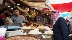 Amman, Jordanië - 2019-04-18 - mens koopt noten van marktbazaar stock footage