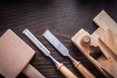 Ammassi gli scalpelli piani della piallatrice del martello ed i mattoni di legno Fotografie Stock