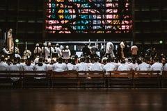 Ammassi in una cattedrale con molti principianti sui banchi di legno Immagine Stock Libera da Diritti