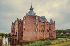 Ammersoyen Castle with its brick towers, wooden bridge, water filled moat and gardens on cloudy day. Near to the historic and vibrant city of s-Hertogenbosch royalty free stock photography