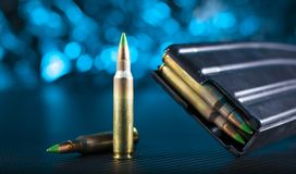 Ammo for an AR-15 and metal magazine. Metal magazine and ammunition for an AR-15 with a blue background Royalty Free Stock Images