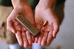 Ammo. A close up view of someone holding an ammo clip and bullet Stock Photography
