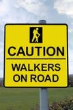 Ammonisca i camminatori sul segnale stradale con il percorso di residuo della potatura meccanica Fotografie Stock