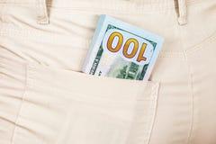 Ammucchi le banconote dei dollari americani nella tasca dei jeans Fotografia Stock Libera da Diritti