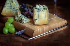 Ammuffito blu maturo ed uva dello stilton del bordo del formaggio Fotografia Stock