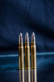 Ammunition on a dark blue background with reflection in a glass. Close up. Weapons. Bullets Stock Photo