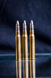 Ammunition on a dark blue background with reflection in a glass. Close up. Weapons. Bullets Stock Photography
