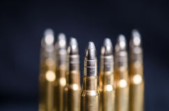 Ammunition on a dark blue background with reflection in a glass. Close up. Weapons. Bullets Stock Image