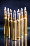 Ammunition on a dark blue background with reflection in a glass. Close up. Weapons. Bullets Royalty Free Stock Photos