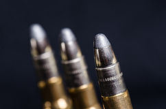 Ammunition on a dark blue background with reflection in a glass. Close up. Weapons. Bullets Stock Photos