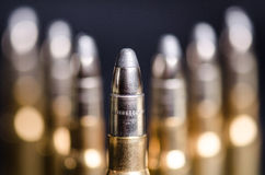 Ammunition on a dark blue background with reflection in a glass. Close up. Weapons. Bullets Royalty Free Stock Photography