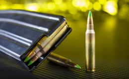 AR-15 bullets and magazine. Ammunition with gree tips that go in an AR-15 and a magazine Royalty Free Stock Photography