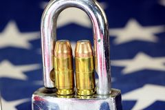 Ammunition and padlock on United States flag - Gun rights and gun control concept Stock Image