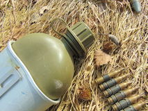 Ammunition from World War 2 and drinking bottle. Laying outside in straw stock photos