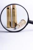 Ammunitionar på en vit bakgrund Sikt till och med en förstoringsapparat isolerat close upp vapen Royaltyfri Fotografi