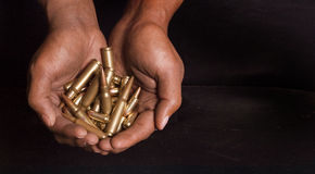Ammunitions. Hands held together with pistol and rifle ammunitions Stock Photography