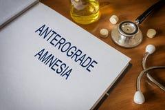Amnésie antérograde écrite sur le livre avec des comprimés Photos libres de droits