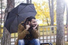 Amn tenant le parapluie se reposant sur un banc Photos stock