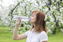 在公园amo喝水一个美丽的少妇的画象 免版税库存照片