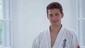 Amo de los artes marciales que sonríe en gimnasio almacen de metraje de vídeo