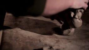 Amo del alfarero del varón adulto que prepara la arcilla en la tabla Vista delantera, primer, manos solamente, irreconocible metrajes