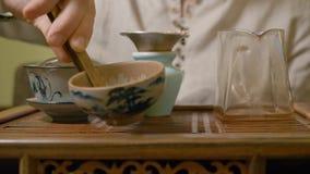 Amo del té de la mano verter nuestro té verde de la primera infusión mientras que ceremonia de té china metrajes