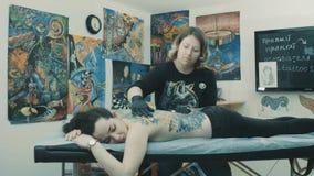 Amo del tatuaje que da masajes a la parte posterior del cliente almacen de metraje de vídeo