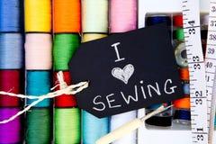 Amo el coser - fondo de los carretes del algodón con la pizarra Fotografía de archivo