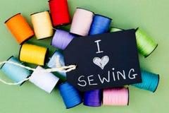 Amo el coser - fondo de los carretes del algodón con la pizarra Imagen de archivo