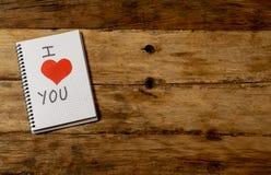 Amo il messaggio con il simbolo rosso del cuore scritto sul blocco note in biglietti di S. Valentino e nella celebrazione di anni immagini stock