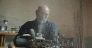 Amo masculino mayor que trabaja en la fábrica de madera con el tronzador que corta la madera almacen de metraje de vídeo