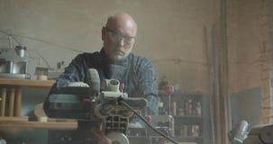Amo masculino mayor que trabaja en la fábrica de madera con el tronzador que corta la madera que es concentrada y seria almacen de video