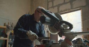 Amo masculino mayor que trabaja en la fábrica de madera con el tronzador y regla que es concentrada y seria almacen de video