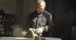 Amo masculino mayor que trabaja en la fábrica de madera que muele con el tronzador al tablero de madera almacen de metraje de vídeo