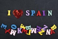 Amo palabra ESPAÑOLA en el fondo negro del tablero compuesto de letras de madera del ABC del bloque colorido del alfabeto, copio  Foto de archivo