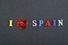 Amo palabra ESPAÑOLA en el fondo negro del tablero compuesto de letras de madera del ABC del bloque colorido del alfabeto, copio  Imagenes de archivo