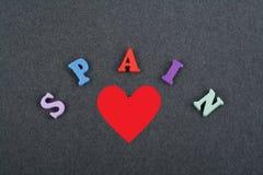 Amo palabra ESPAÑOLA en el fondo negro del tablero compuesto de letras de madera del ABC del bloque colorido del alfabeto, copio  Imágenes de archivo libres de regalías
