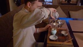 Amo que prepara té japonés en la tabla de té mientras que ceremonia tradicional metrajes