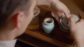 Amo que vierte la infusión del té verde de gaiwan en cuenco Ceremonia de té china metrajes