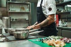 Amo vista lateral de la comida italiana de las manos del cocinero joven con los tatuajes que cocina las pastas italianas hechas e imagen de archivo
