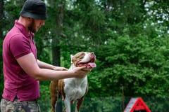 Amo y su perro obediente en un centro de formación del perro imagenes de archivo