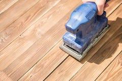 Amoladora azul en piso de madera imagenes de archivo