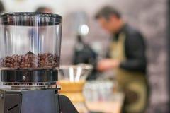Amoladora de café con el camarero borroso en el fondo imagen de archivo libre de regalías