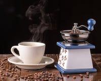 Amoladora de café del vintage y taza de café mecánicas en la tabla Fotografía de archivo