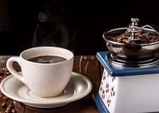 Amoladora de café del vintage y taza de café mecánicas en la tabla Imágenes de archivo libres de regalías