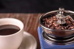Amoladora de café del vintage y taza de café mecánicas en la tabla Foto de archivo libre de regalías
