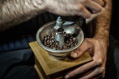 Amoladora de café de madera del vintage con los granos de café en las manos de un hombre imagenes de archivo