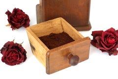 Amoladora de café manual con las rosas en un fondo blanco antiquary fotos de archivo