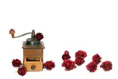 Amoladora de café manual con las rosas en un fondo blanco antiquary imagen de archivo