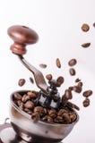 Amoladora de café manual con los granos de café Fondo blanco Estilo moderno Granos de café asados Granos de café de la levitación Fotografía de archivo libre de regalías
